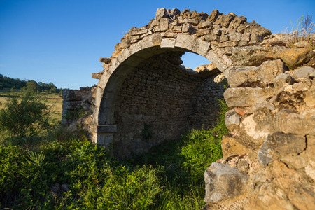 weed block: Ruins of an ancient shrine and overgrown vegetation. Remains of an arch and part of the walls of the vault Stock Photo