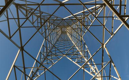 Electricity distribution tower seen from below on blue sky background - Torre de distribucion de electricidad vista desde abajo sobre fondo de cielo azul   torre electrica, torre, electricidad, torreta, metalico, metal, cables, cielo, azul, despejado,