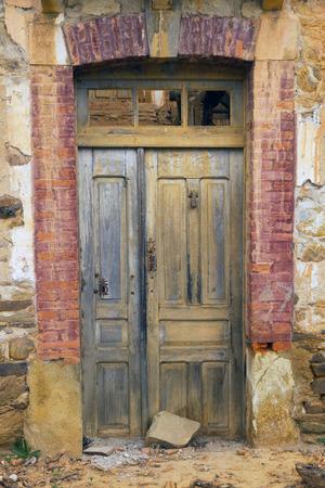 caller: Old wooden door, muddy, with the caller, and rusty locks, in a country house in ruins - Antigua Puerta de madera, manchada de barro, con llamador, y cerraduras oxidadas, en casa rustica en ruinas  puerta; antigua; rustica; madera; ruina,  llamador; man Stock Photo