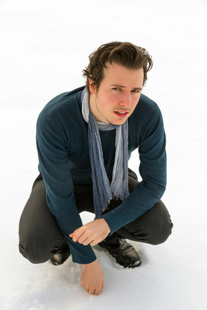 beardless: Portrait of young man from above. Looking at camera and squat, with sweater and blue scarf around his neck, isolated on snowy background Stock Photo