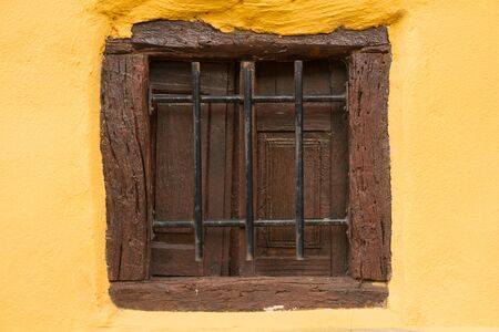 rejuvenated: Small window of old wood, recently revamped, restored and painted, with small iron bars