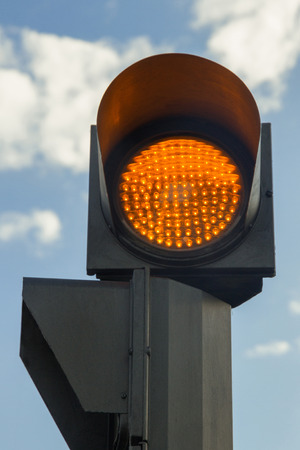 amber light: Traffic light on amber or orange light of day, with blue sky background, announcing its way to pedestrians Stock Photo