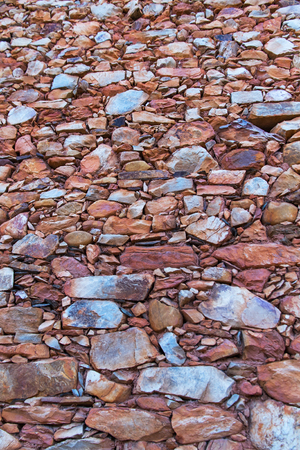 красноватый: Stone wall texture edges and slabs in traditional construction, with reddish tones Фото со стока
