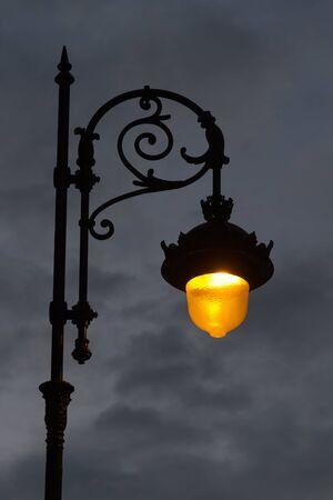 Streetlight urban lighting lit classic style, at dawn or dusk on a cloudy gray sky