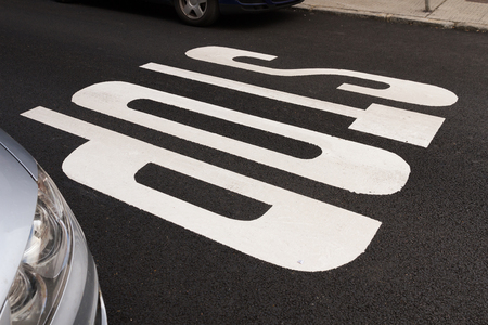 markings: Stop road markings, painted in white on the asphalt Between two cars, parked Stock Photo