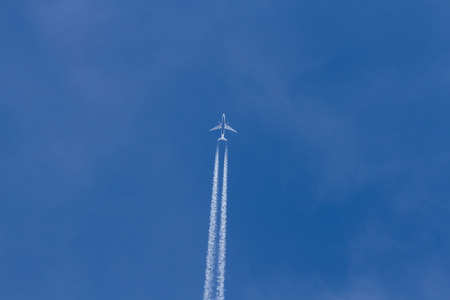 fly: Jet plane flying in the blue sky. Wake leaving trace or steam jet, viewed from below in nadir shot Stock Photo