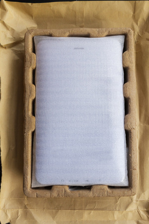 box: New digital tablet, packaged in carton and wrapped in protective pouch before Being released. View from the back side. Isolated on black background