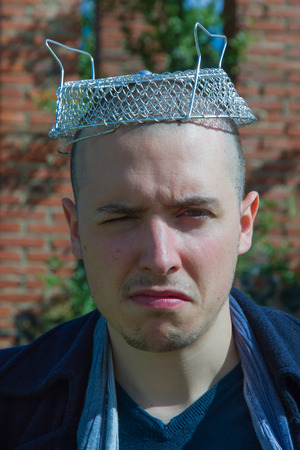 cocky: Young man with a cooking utensil metal strainer hat as pressure cooker. With humorous, skeptical and cocky gesture and crazy