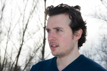 beardless: Half length portrait of young man, beardless and disheveled. In profile and looking in the distance, with white sky background and trees