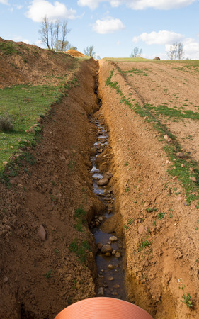ditch: Long ditch or sewer Recently built on the edges of a path of clay soil. Excavation line pipe in the foreground to channel water