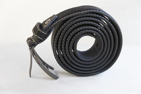 espiral: cintur�n de cuero negro enrollado en espiral con hebilla en tono plateado cromo, aislado en fondo blanco