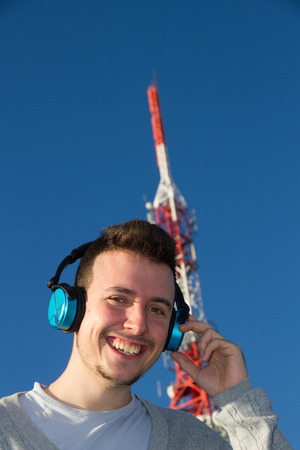 beardless: Cheerful and smiling young man with earphones or headphones next to a telecommunications antenna