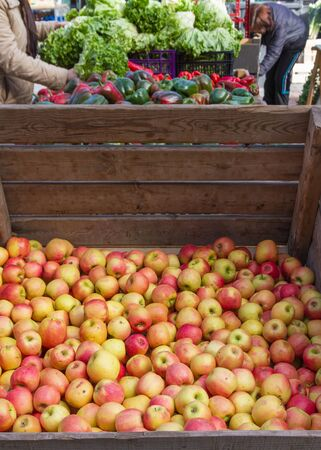 market bottom: Drawer with apples in bulk in a market stall outdoors and other products at the bottom
