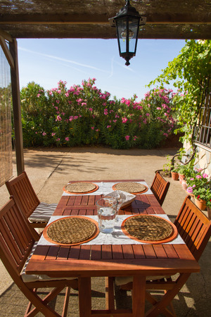 Wooden table prepared for four people with chairs, outside garden of a house. On the table a basket with bread, and a glass jar with water, tablecloths and dishes Rests. Surrounded by flowers azalea