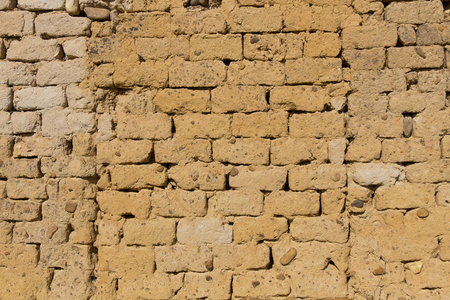 adobe wall: Wall for background or texture of adobe mud and straw bricks baked in the sun, encrusted with stones