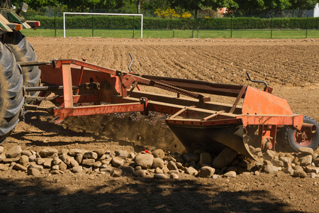 cleanser: Rake stones cleanser machine, pulled by a tractor, separating or removing the stones of the land, In This case paving the way for the construction of a football field Stock Photo