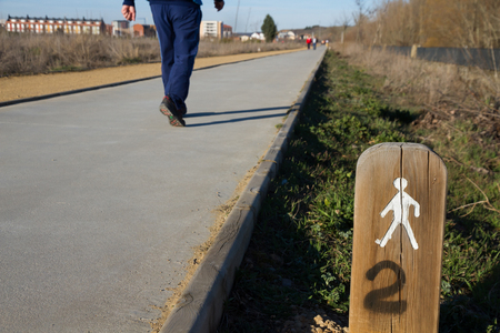 stated: People cycling and walking through a pedestrian and bike lane on the outskirts of a city and the winter sun. With Stated or milepost sign in the foreground