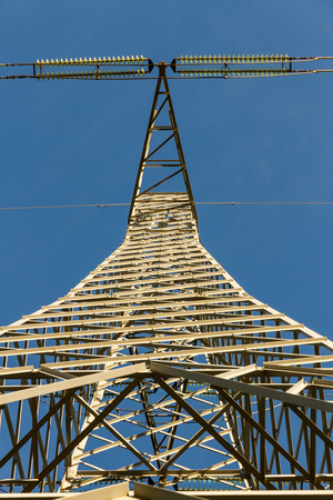 from below: Electricity distribution tower seen from below on blue sky background Stock Photo