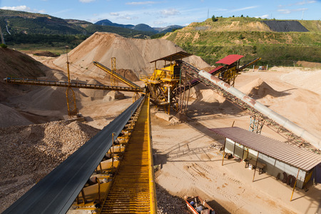 classifier: Gravel pit in mountain area with gravel machinery and distribution tapes ACCORDING sizes, lots of gravel and sand for construction industry Stock Photo