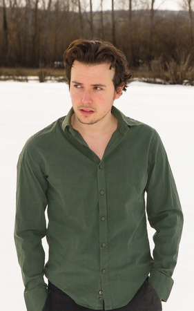 medium length: Portrait of medium length body of young man in shirt, shaven and disheveled. Looking to His right, His hands in pockets. With white sky background and winter trees Stock Photo