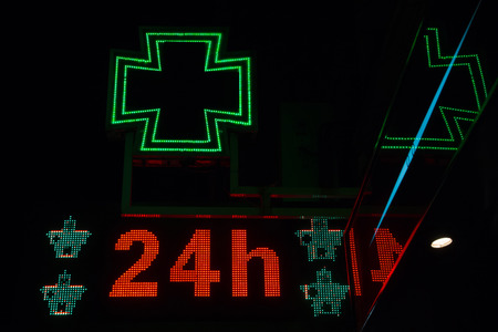 24 hours: Bright night pharmacy sign on. With the message open 24 hours a day Between junctions