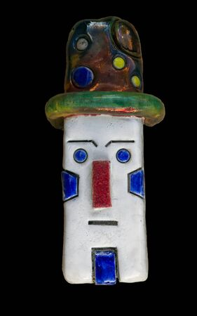 Artistic figure of stoneware raku ceramics technique. Human rectangular white clown face and polka dots hat with. Isolated on black background