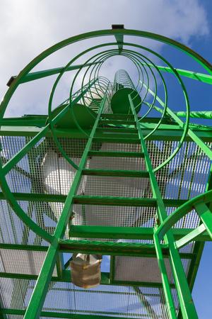 fibra de vidrio: escalera de metal verde vertical. Silo para el almacenamiento de la sal del camino con vistas a la temporada de nieve. Escalera al cielo azul con nubes con barandillas de seguridad y pantallas de aterrizajes. Escalera al cielo Foto de archivo