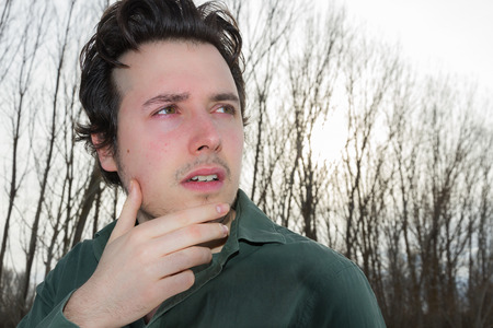 beardless: I young man is looking to His left and up, with hand on chin and green shirt, in a winter landscape with trees without ojas and cloudy sky
