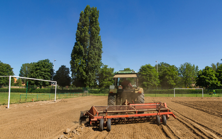 Tractor cleanser lowering the rake stones to separate or remove the stones of the land. Construction of a football field