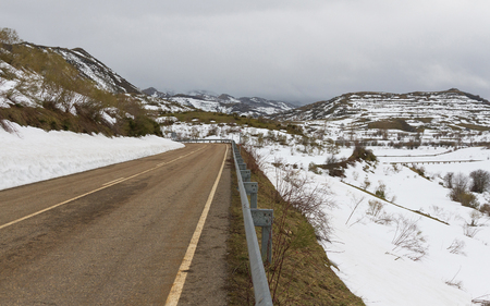 guardrails: Winter mountainous landscape with two-lane road curved and protective barriers or guardrails