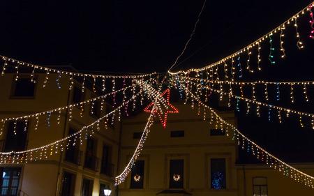 estrella de belen: Las luces de Navidad en la ciudad de noche con la estrella de Belén en el medio - Iluminación navideña en nocturno de ciudad con Estrella de Belen en El Centro  luces, navidad, estrella, ciudad, colores, noche, farolas, ventanas, Edificios, centro, rojo, Puntos de Encuentro,