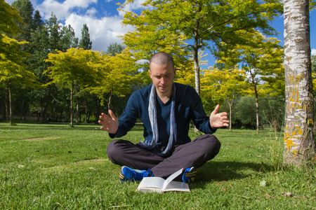 implementing: Young man with cropped hair sitting on the grass in a park with legs crisscrossed Implementing and following instructions or from a book