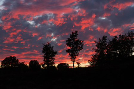 Beautiful sunset at dusk in summer. Oak Hill landscape. Heaven reds and grays with fire Stock Photo