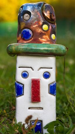 Artistic ceramic stoneware figure With raku technique. Human rectangular white clown face and hat with polka dots