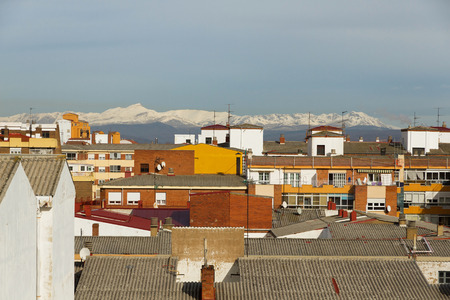 Telephoto lens roofs and rooftops of town with mountains in the background Snowfall