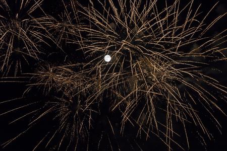 Fireworks in night of super full moon in perigee. Real image -  Fuegos artificiales en noche de super luna llena en perigeo. Imagen real   luna llena, fuegos artificiales, noche,fiesta, espectaculo, fiesta, chispas, dorado, negro, perigeo, superluna, p Reklamní fotografie