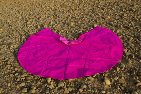 Pink cape worn by bullfighters, spread on reddish earth with boulders