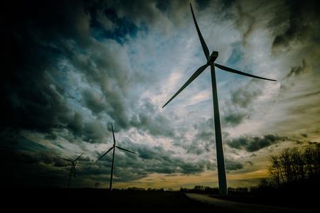Wind turbines with blades moving with sky background with clouds. Photographic treatment of color with dark vignette - Aerogeneradores sobre fondo de cielo con nubes. Tratamiento fotografico del color con viñeta oscura /// aerogenerador, palas,  energía