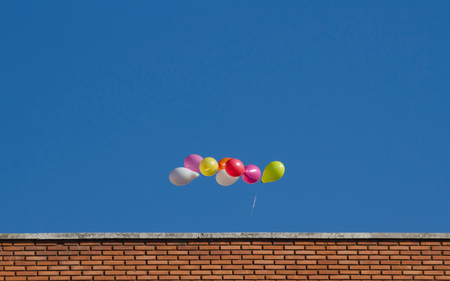 cleared: Colorful balloons flying through the air, above the top of a building