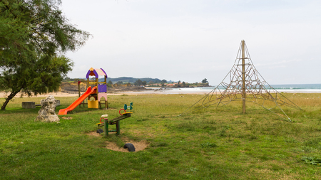 Playground for children in green meadow beside the sea, on the beach, with slide, rocking, and pyramid climbing structure