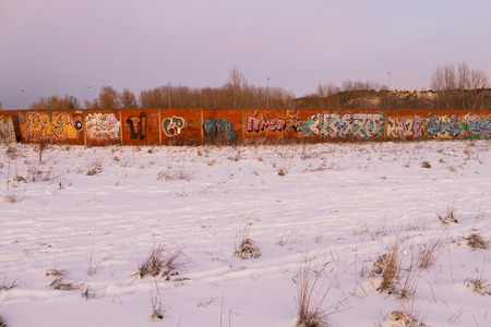 Landscape snowy to the sunset with a wall of brick full of graffiti. Grove of poplars in the background