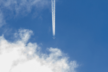 Jet airplane flying in the blue sky with clouds. Wake leaving trace or steam jet, viewed from below 스톡 콘텐츠