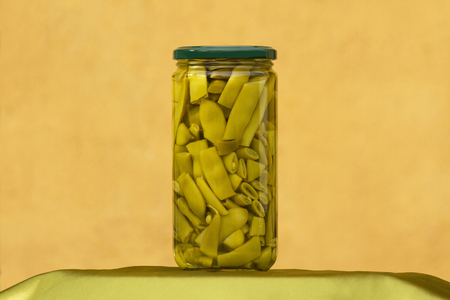 Jar or glass container showing green canned beans with ocher wall background 스톡 콘텐츠