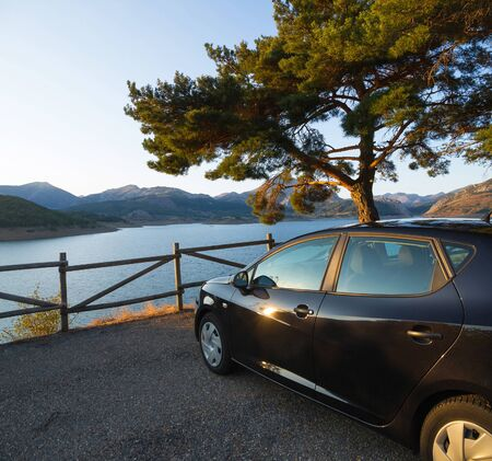 Side black car, parked in a rest area, viewpoint, or lookout road, in the shade of a tree and fence of wooden posts. Against the backdrop of mountains and lake or swamp