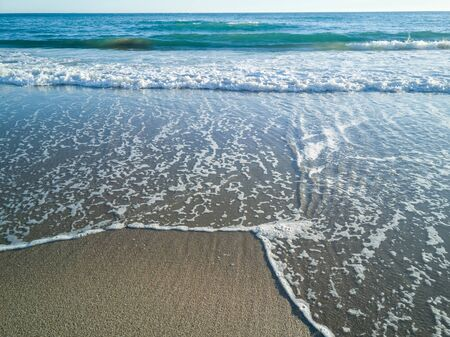 The waves of the sea reaching the sand
