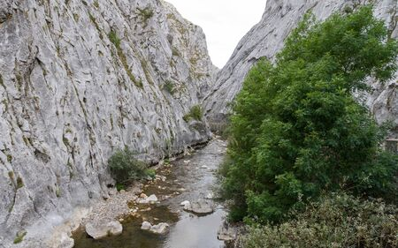 River and road with retaining walls on the edge, in a narrow gorge between stone mountains