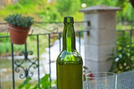 Glass vase and bottle of Cider (fermented apple juice). On outdoor bar terrace and unfocused background