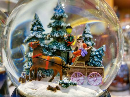 Crystal balls with landscape of snowy fir trees and characters in horse carriage