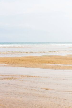 Detail of wide empty beach plain with clear wet sand and sea waves coming in gently Imagens