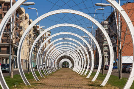Pedestrian walk through the center of an avenue, protected by a mesh of cables intertwined between white semicircular metal arches that simulate a tunnel Editorial